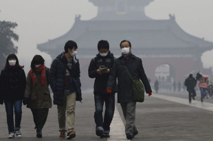 epa05059018 Visitors wearing protective masks against smog take a tour of Temple of Heaven Park in Beijing, China, 08 December 2015. City schools closed on 08 December as Beijing issued its first-ever smog red alert, advising residents to stay indoors and children not to go to school until 10 December lunchtime. The new alert issued by the city's emergency management headquarters represented the highest-level warning issued for the first time since a four-colour scale was introduced in 2013.  EPA/ROLEX DELA PENA